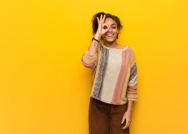 Młoda czarna amerykanin afrykańskiego pochodzenia dziewczyna z niebieskimi oczami ufnymi robi ok gestowi na oku