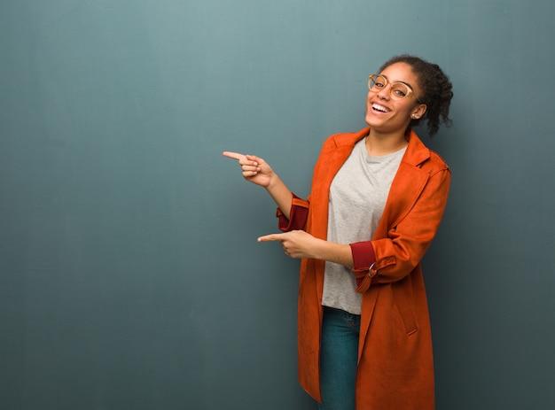 Młoda czarna amerykanin afrykańskiego pochodzenia dziewczyna z niebieskimi oczami wskazuje strona z palcem