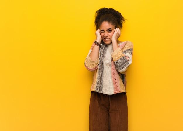 Młoda czarna amerykanin afrykańskiego pochodzenia dziewczyna z niebieskimi oczami zakrywa ucho z rękami