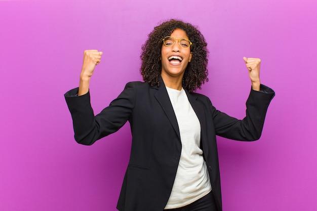 Młoda czarna biznesowa kobieta czuje się szczęśliwa, pozytywna i udana, świętuje zwycięstwo, osiągnięcia lub szczęście