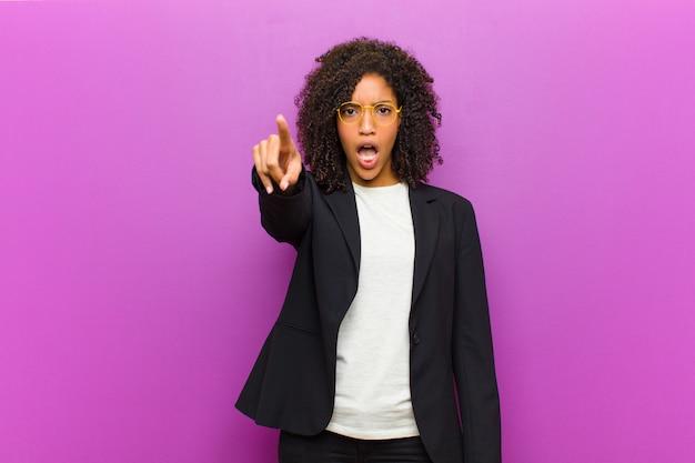 Młoda czarna biznesowa kobieta czuje się zszokowana i zaskoczona, wskazując i patrząc w podziw z zachwytem z otwartymi ustami