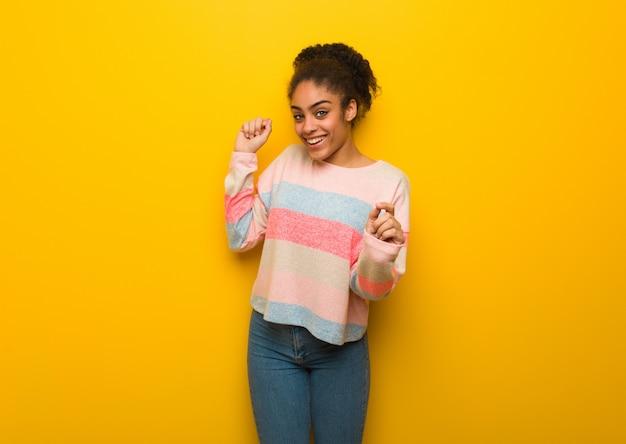 Młoda czarna dziewczyna afroamerykanów o niebieskich oczach, taniec i zabawę