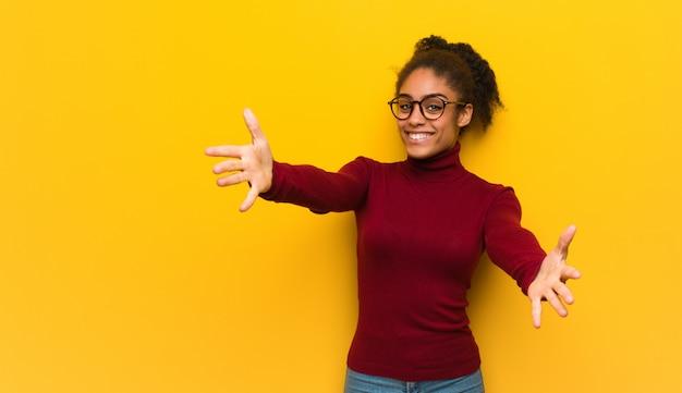 Młoda czarna dziewczyna afroamerykanów o niebieskich oczach zapraszających do przyjazdu