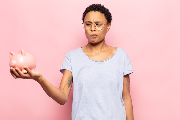 Młoda czarna kobieta afro czuje się smutna, zdenerwowana lub zła i patrzy w bok z negatywnym nastawieniem, marszcząc brwi w niezgodzie