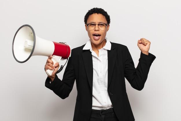 Młoda czarna kobieta afro krzycząca agresywnie z gniewnym wyrazem twarzy lub z zaciśniętymi pięściami świętująca sukces