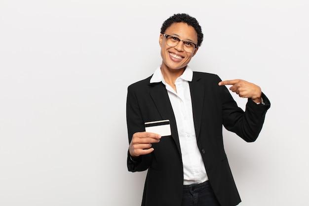 Młoda czarna kobieta afro uśmiecha się radośnie, czuje się szczęśliwa i wskazuje na bok i do góry, pokazując obiekt w przestrzeni kopii