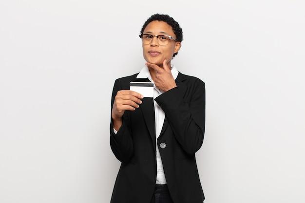 Młoda czarna kobieta afro uśmiecha się radośnie i marzy lub wątpi, patrząc w bok