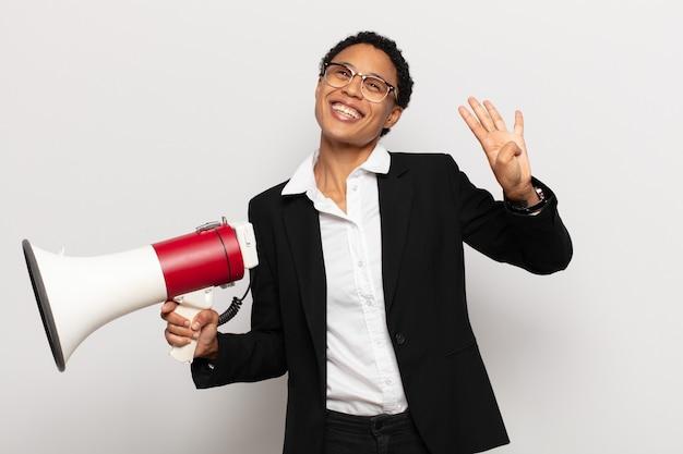 Młoda czarna kobieta afro uśmiechnięta i wyglądająca przyjaźnie, pokazująca cyfrę cztery lub czwartą z ręką do przodu, odliczając w dół