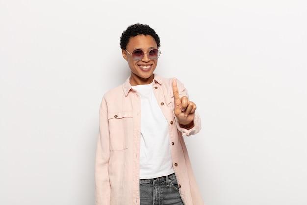 Młoda czarna kobieta afro uśmiechnięta i wyglądająca przyjaźnie, pokazująca numer jeden lub pierwsza z ręką do przodu, odliczająca w dół