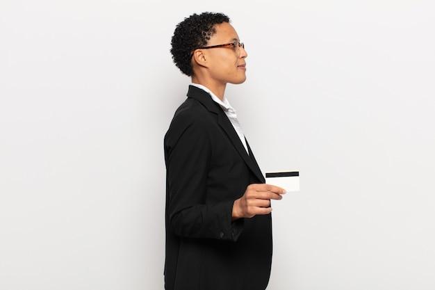 Młoda czarna kobieta afro w widoku profilu chce skopiować przestrzeń do przodu, myśleć, wyobrażać sobie lub marzyć