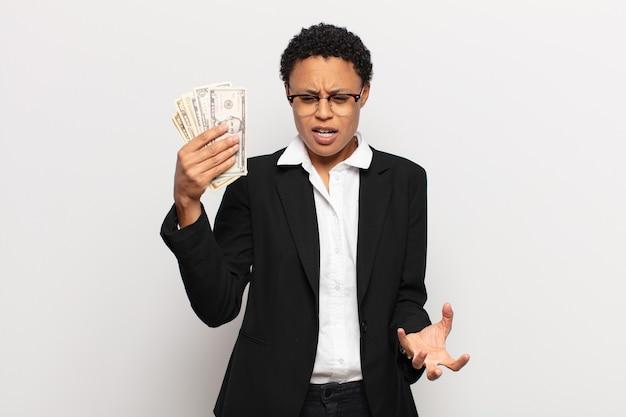 Młoda czarna kobieta afro wyglądająca na złą, zirytowaną i sfrustrowaną krzyczącą wtf lub co jest z tobą nie tak