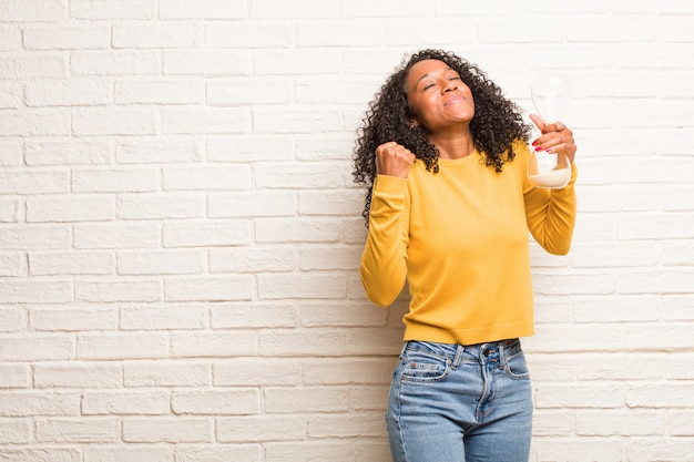 Młoda czarna kobieta bardzo szczęśliwa i podekscytowana, podnosząc ręce, świętując zwycięstwo lub sukces, wygrywając na loterii