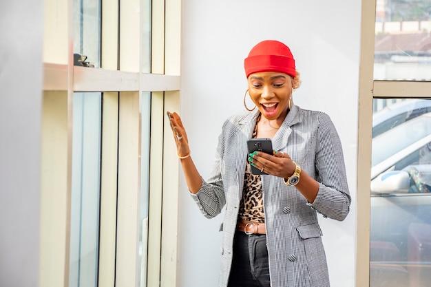 Młoda czarna kobieta biznesu czuje się podekscytowana i zaskoczona, patrząc na swój telefon komórkowy