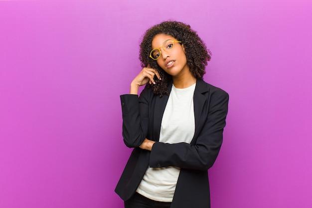 Młoda czarna kobieta biznesu o skoncentrowanym spojrzeniu, zastanawiającym się z wątpliwym wyrazem, patrząca w górę i na bok
