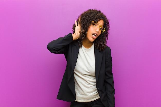 Młoda czarna kobieta biznesu wyglądająca poważnie i ciekawie, słuchająca, próbująca usłyszeć tajną rozmowę lub plotkę, podsłuchująca