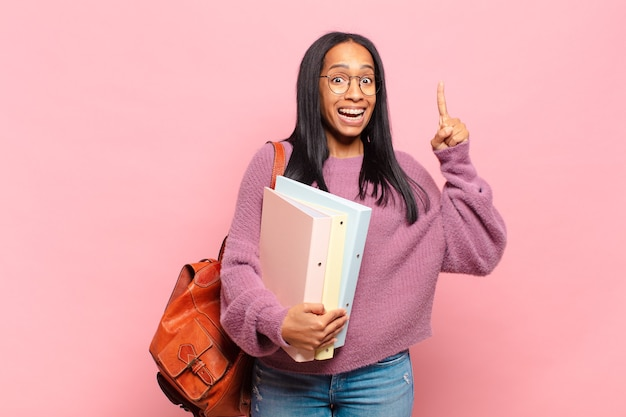 Młoda czarna kobieta czując się jak szczęśliwy i podekscytowany geniusz po zrealizowaniu pomysłu, radośnie podnosząc palec, eureka!. koncepcja studenta