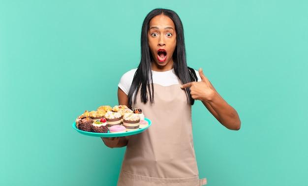 Młoda czarna kobieta czująca się szczęśliwa, zaskoczona i dumna, wskazująca na siebie z podekscytowanym, zdumionym spojrzeniem. koncepcja szefa kuchni piekarni