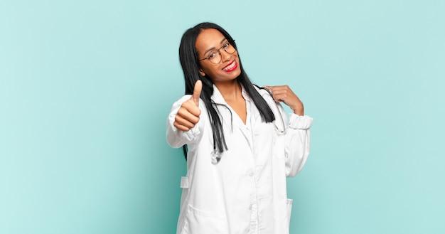 Młoda czarna kobieta czuje się dumna, beztroska, pewna siebie i szczęśliwa, uśmiechając się pozytywnie z kciukami do góry. koncepcja lekarza