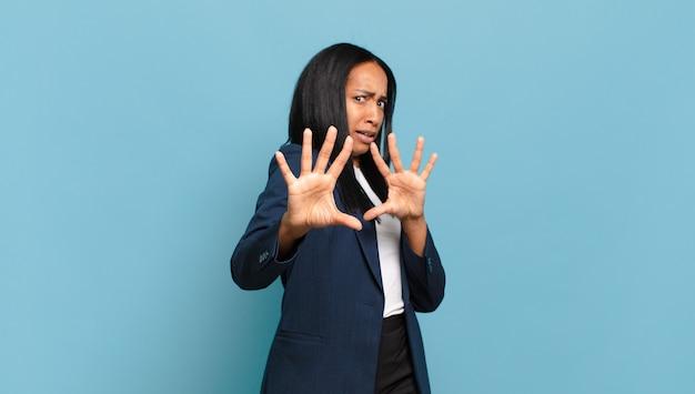 Młoda czarna kobieta czuje się przerażona, cofa się i krzyczy z przerażenia i paniki, reagując na koszmar. pomysł na biznes