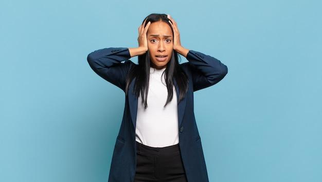 Młoda czarna kobieta czuje się przerażona i zszokowana, podnosi ręce do głowy i panikuje z powodu błędu. pomysł na biznes