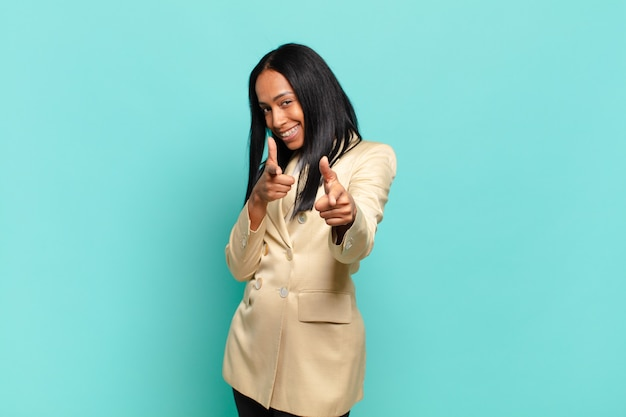 Młoda czarna kobieta czuje się szczęśliwa, fajna, zadowolona, zrelaksowana i odnosząca sukcesy, wskazując na kamerę, wybierając ciebie. pomysł na biznes