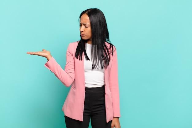 Młoda czarna kobieta czuje się szczęśliwa i uśmiecha się od niechcenia, patrząc na przedmiot lub koncepcję trzymaną na dłoni z boku. pomysł na biznes