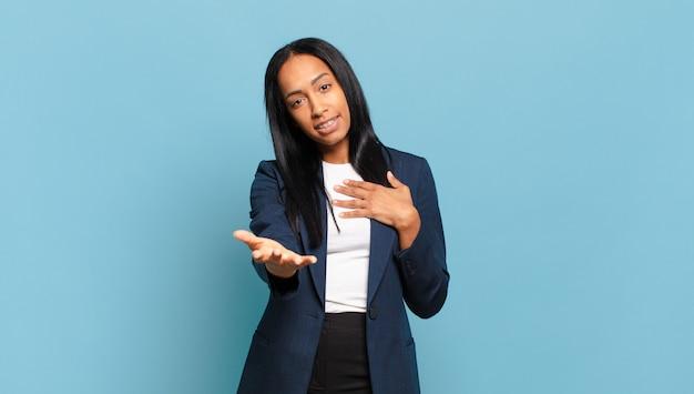 Młoda czarna kobieta czuje się szczęśliwa i zakochana, uśmiechając się jedną ręką przy sercu, a drugą wyciągniętą do przodu. pomysł na biznes