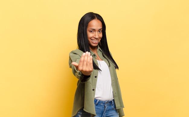 Młoda czarna kobieta czuje się szczęśliwa, odnosząca sukcesy i pewna siebie