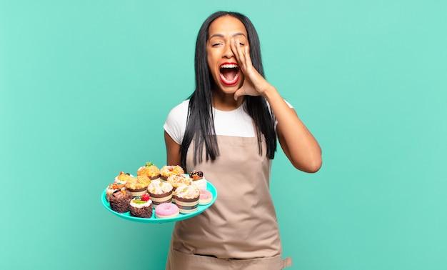 Młoda czarna kobieta czuje się szczęśliwa, podekscytowana i pozytywna, wydając wielki okrzyk z rękami przy ustach, wołając. koncepcja szefa kuchni piekarni