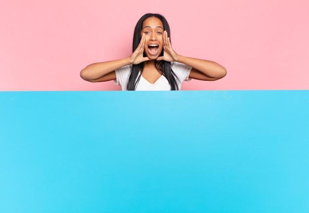 Młoda czarna kobieta czuje się szczęśliwa, podekscytowana i pozytywna, wydając wielki okrzyk z rękami przy ustach, wołając. kopia koncepcja przestrzeni