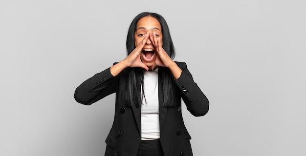 Młoda czarna kobieta czuje się szczęśliwa, podekscytowana i pozytywna, wydając wielki okrzyk z rękami przy ustach, wołając. pomysł na biznes