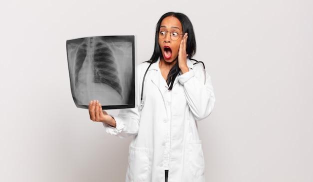 Młoda czarna kobieta czuje się szczęśliwa, podekscytowana i zaskoczona, patrząc w bok z obiema rękami na twarzy. koncepcja lekarza