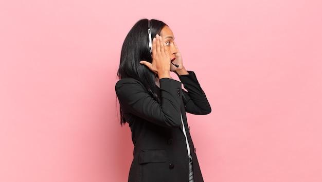 Młoda czarna kobieta czuje się szczęśliwa, podekscytowana i zaskoczona, patrząc w bok z obiema rękami na twarzy. koncepcja telemarketingu