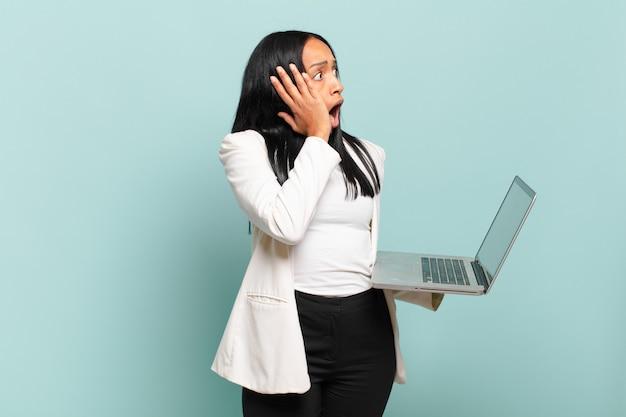 Młoda czarna kobieta czuje się szczęśliwa, podekscytowana i zaskoczona, patrząc w bok z obiema rękami na twarzy