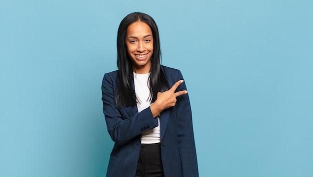 Młoda czarna kobieta czuje się szczęśliwa, pozytywna i odnosząca sukcesy, z ręką tworzącą kształt litery v nad klatką piersiową, pokazując zwycięstwo lub pokój. pomysł na biznes