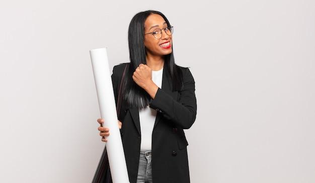 Młoda czarna kobieta czuje się szczęśliwa, pozytywna i odnosząca sukcesy, zmotywowana, gdy staje przed wyzwaniem lub świętuje dobre wyniki. koncepcja architekta