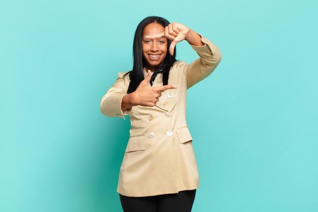 Młoda czarna kobieta czuje się szczęśliwa, przyjazna i pozytywna, uśmiecha się i robi z rąk portret lub ramkę na zdjęcia. pomysł na biznes