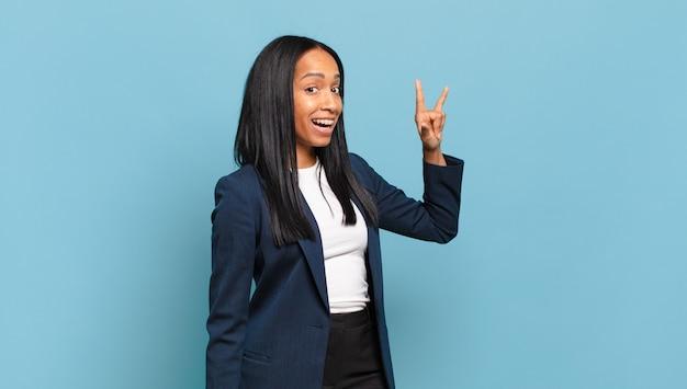Młoda czarna kobieta czuje się szczęśliwa, zabawna, pewna siebie, pozytywna i buntownicza, wykonując ręką rockowy lub heavy metalowy znak. pomysł na biznes