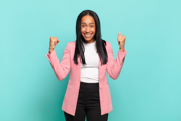 Młoda czarna kobieta czuje się szczęśliwa, zaskoczona i dumna, krzycząc i świętując sukces z wielkim uśmiechem.