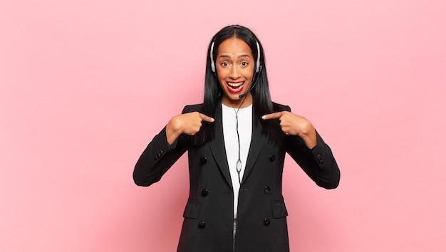 Młoda czarna kobieta czuje się szczęśliwa, zaskoczona i dumna, wskazując na siebie z podekscytowaniem