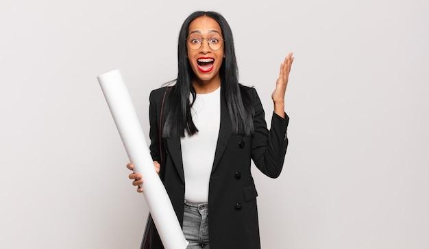 Młoda czarna kobieta czuje się szczęśliwa, zaskoczona i pogodna, uśmiechnięta z pozytywnym nastawieniem, realizująca rozwiązanie lub pomysł. koncepcja architekta