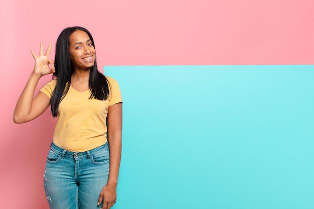 Młoda czarna kobieta czuje się szczęśliwa, zrelaksowana i zadowolona, okazując aprobatę dobrym gestem, uśmiechając się. kopia koncepcja przestrzeni