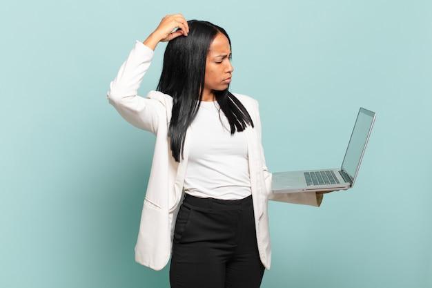 Młoda czarna kobieta czuje się zakłopotana i zdezorientowana, drapiąc się po głowie i patrząc w bok. koncepcja laptopa