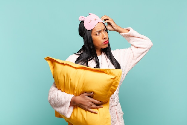 Młoda czarna kobieta czuje się zakłopotana i zdezorientowana, drapiąc się po głowie i patrząc w bok. koncepcja piżamy