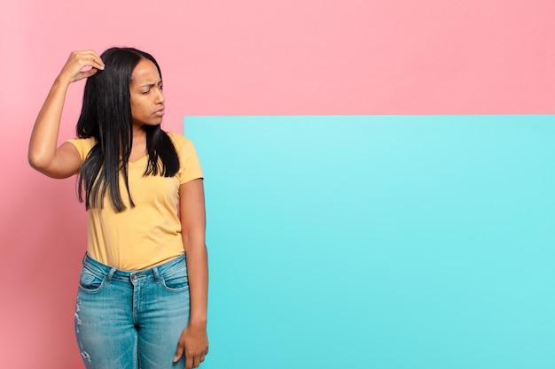 Młoda czarna kobieta czuje się zakłopotana i zdezorientowana, drapiąc się po głowie i patrząc w bok. kopia koncepcja przestrzeni