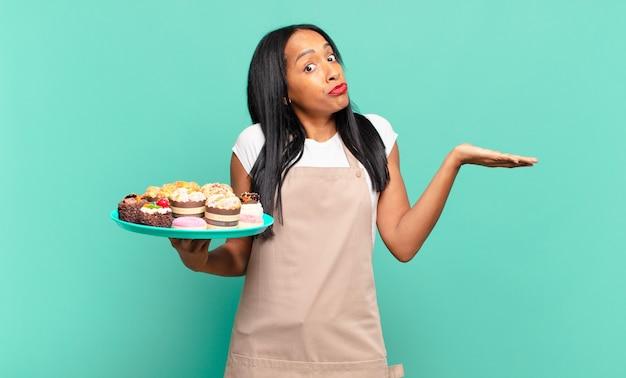 Młoda czarna kobieta czuje się zakłopotana i zdezorientowana, wątpi, waży lub wybiera różne opcje z zabawnym wyrazem twarzy. koncepcja szefa kuchni piekarni