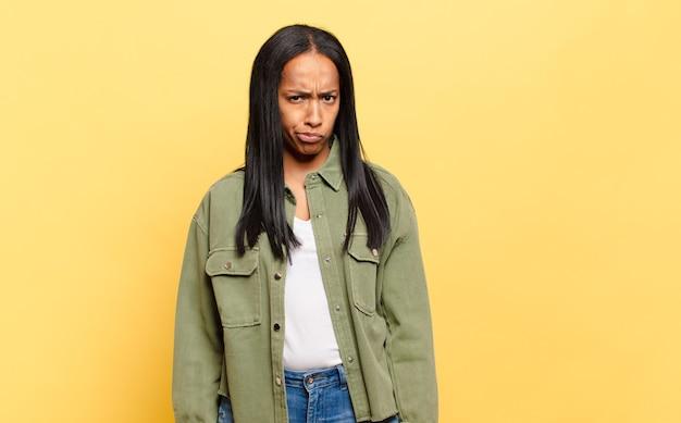 Młoda czarna kobieta czuje się zdezorientowana i wątpi, zastanawia się lub próbuje wybrać lub podjąć decyzję