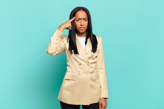 Młoda czarna kobieta czuje się zdezorientowana i zdezorientowana, pokazując, że jesteś szalony, szalony lub oszalały. pomysł na biznes