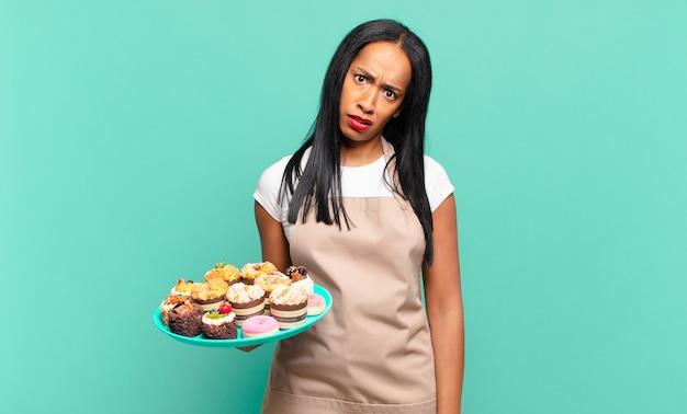 Młoda czarna kobieta czuje się zdezorientowana i zdezorientowana, z tępym, oszołomionym wyrazem twarzy, patrzącą na coś nieoczekiwanego. koncepcja szefa kuchni piekarni