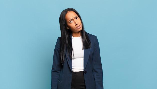 Młoda czarna kobieta czuje się zdezorientowana i zdezorientowana, z tępym, oszołomionym wyrazem twarzy, patrzącą na coś nieoczekiwanego. pomysł na biznes